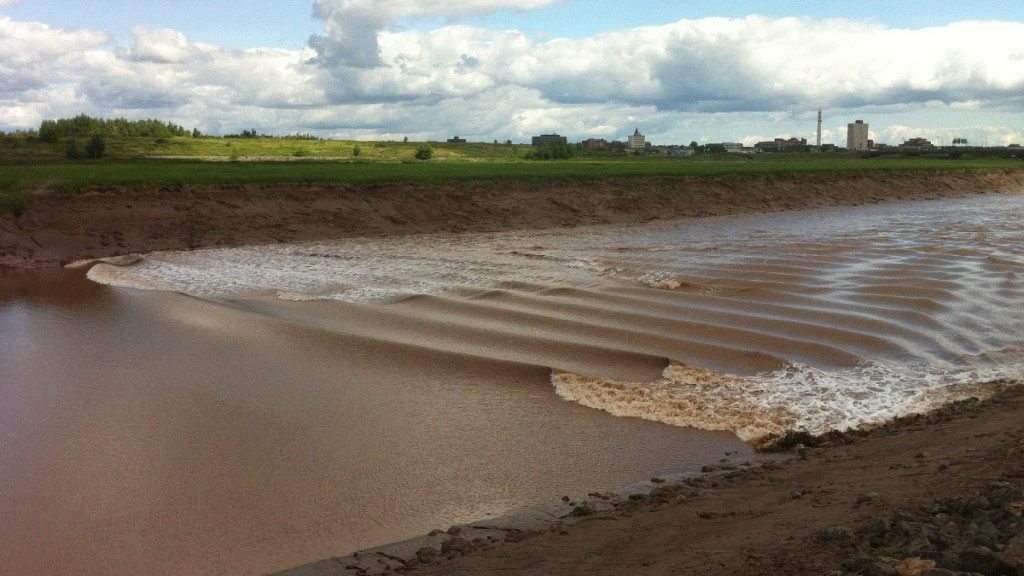 The Tidal Bore flows up the Peticodiac River through Riverview. Moncton can be seen in the distance.