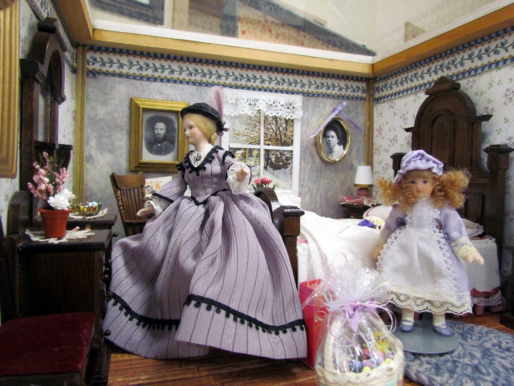 A Victorian bedroom scene, a woman and child preparing for a day out in the Spring. A wonderful miniature from June Aud.